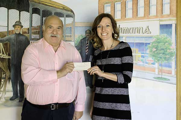 Museum Curator Gary Levitt recently presented Run Club founder Mandy Wiemerskirch with a check for $1,000.  (DHI Media/Nancy Spencer)