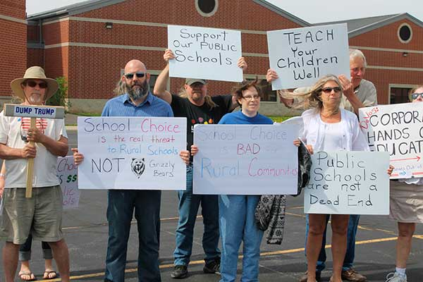 Protesters representing grassroots anti-Trump groups took a corner of the parking lot at Van Wert Middle School Thursday during a visit by United States Department of Education Director Betsy DeVos. (DHI Media/Nancy Spencer)