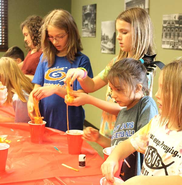 Alivia Hines, left, Alaina Martin, Makayla Hines and Addison Martin work on Pumpkin Guts Slime. (DHI Media/Nancy Spencer)