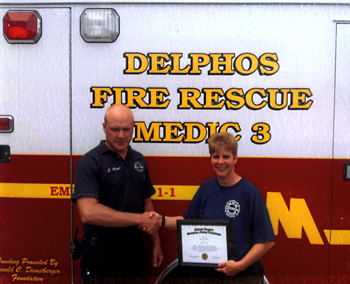 The newest Delphos Fire and Rescue paramedic in Delphos, Diane Pack, accepts her paramedic certificate from Firefighter/Paramedic Cory Meyer. Pack said Meyer was instrumental in her success in earning the designation. (Submitted photo)