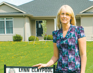 Lynn Claypool, a real estate agent, stands with one of her signs.