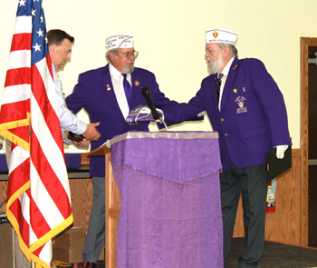 Fort Jennings Mayor Jim Smith, left, receives the award from Purple Heart Association members Bud Hanna, center, and Dave Bower, right, declaring the village of Fort Jennings a Purple Heart Village during the banquet held at the American Legion Post 715 on Tuesday afternoon. (Delphos Herald/Stephanie Groves)