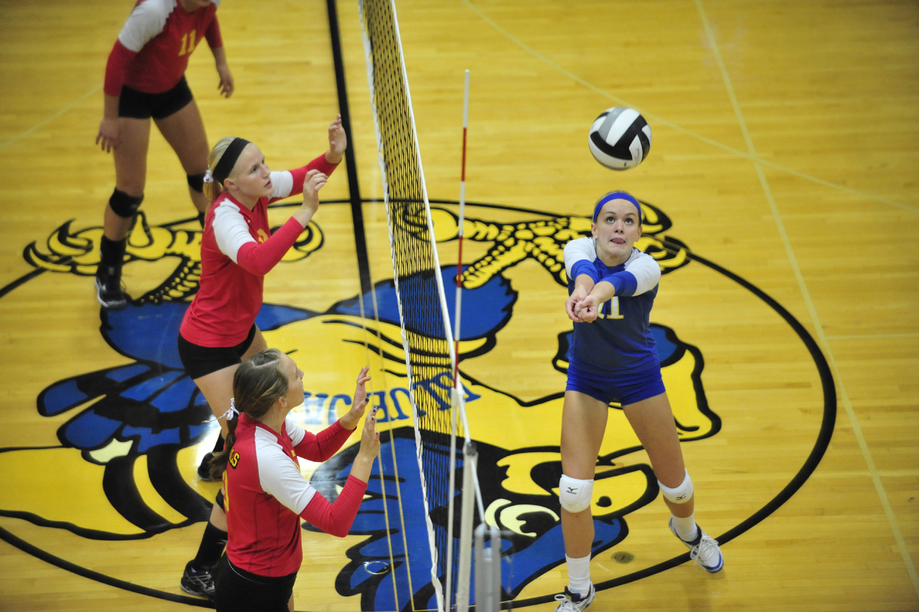 St. John's senior Lauren Utrup keeps the volley going during MAC volleyball action Thursday at Arnzen Gymnasium as New Bremen's Karli Jones and Haley Moeller await the action. The visiting Cardinals swept the Jays.
