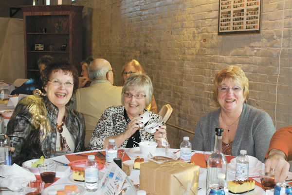 "Rita Suever, left, Janet Kroeger and Sue Trentman enjoy themselves at the Postal Museum Gala Sunday. Kroeger just opened her special ""parcel"" to find a sweet treat inside."