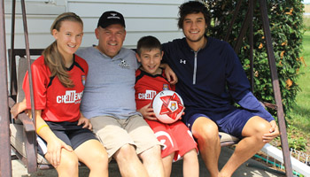 Martin Harris, right, sits with some members of his host family: from left, Carly, Nate and Pete Ankerman; at the Ankerman home. Harris is here promoting the Challenger British Soccer Camps, one of which will be held at the St. John's Annex July 22-26 and where he will be the head instructor. (Delphos Herald/Jim Metcalfe)
