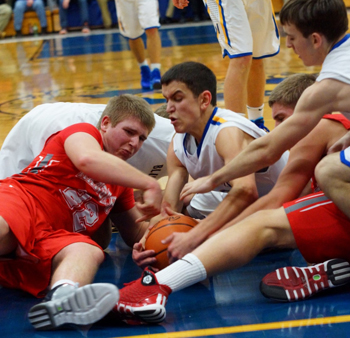 St. John's senior Eric Clark battles for a loose ball with two New Knoxville players — with two Blue Jay teammates also in the fray — Friday night at Arnzen Gym. (Delphos Herald/Randy Shellenbarger)