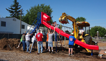 Above: Kiwanis members, city workers and a representative from Marbletown Festival installed a new slide at Garfield Park Saturday morning. Workers include, in no order, Denny Elwer, Cindy Elwer, Jamey Wisher, Mark Brandehoff, Mark Miller, Cindy Metzger, Jim Fischer, Jim Knebel, Dave Smith, Jim Fortener, Ron Grothaus, Adam Wisher, Dave Casemeier and John Clark. Below left: Ty Rudasill takes the inaugural trip down the slide early Saturday afternoon. (DHI Media/Nancy Spencer)
