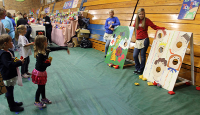St. John's Elementary School held its annual Children's Festival Wednesday afternoon. Students, parents and grandparents spent some quality time together playing games like Plinko, Ring Toss, Bean Bag Toss and Fish Pond. Above: Pre-kindergartener Faith Cross tries her skill at Bean Bag Toss. (Delphos Herald/Stephanie Groves)